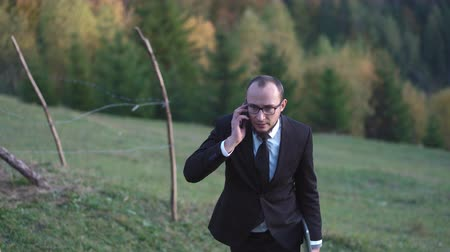 A Man In A Suit Rises Up The Hill And Speaks On The Phone. He Carries A Laptop In His Hand. Business Concept Video