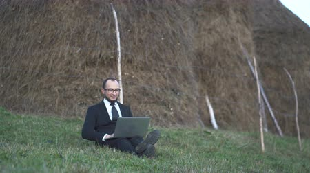 zöld fű : A Male Manager Works On A Laptop Outdoors In The Mountains. He Smiles Because He Is Successful. Business Concept Video Stock mozgókép