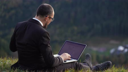A Man In Glasses And A Suit Sits On A Hill And Works On His Laptop. A Young Man Holds A Laptop On His Lap. Business Concept Video
