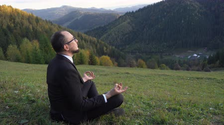 Manager In An Office Suit Meditates In The Mountains. A Man Reaches Zen And Relaxes. Business Concept Video