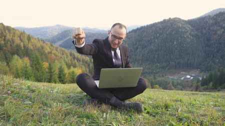 An Adult Man Got An Idea When He Was Sitting On The Hills. A Man In A Suit And With A Laptop On His Lap. Business Concept Video