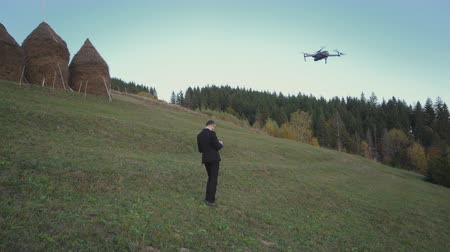 Tourist Businessman Launches His Drone In The Mountains To Take Pictures And Video Of The Beauty Around. He Controls The Drone From The Remote Control. Drone Operator Concept