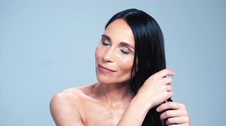 Charming Woman With Naked Shoulders Tidying Her Hair While Posing In Front Of The Camera On The Grey Background. Close-up Shot