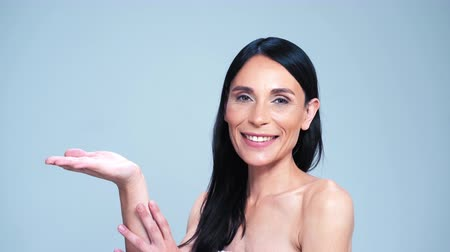 Pretty Woman With Naked Shoulders Is Raising One Hand Up With A Palm Uppermost. The Other Hand Is Laying On The Wrist. The Charming Brunette Is Posing On The Isolated Grey Background.