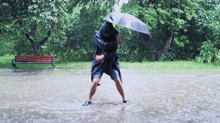 The Man In Shorts And Raincoat Is Dancing Very Actively Under The Heavy Rain. The Dancer Is Holding Umbrella In His Hand. The Green Trees Are On The Background