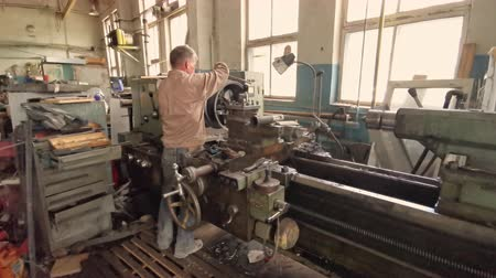 csavarkulcs : The Middle-Aged Turner Standing With His Back Works At The Turning Workstation In The Production Department
