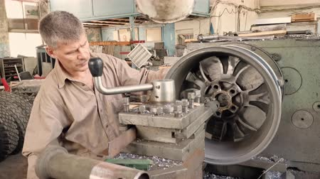 csavarkulcs : The Elderly Turner Rotates The Alloy Wheel Rim Installed On The Turning Workstation In The Fabrication Shop.