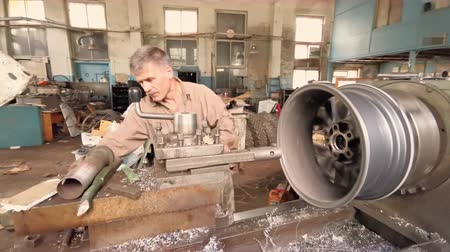 alaşım : The Middle- aged Turner In The Fabrication Shop Measures The Diameter Of The Rim Center Bore With The Inside Calipers Stok Video