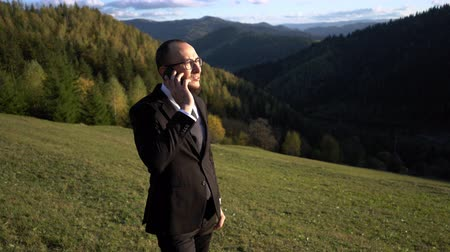 A Man In A Suit Calls On The Phone And Speaks With A Client While He Is In The Mountains. Middle-aged Businessman Makes A Deal While On A Hill. Business Concept Video Vídeos