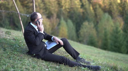 A Middle-aged Businessman In Glasses And A Black Suit Speaks On The Phone While Sitting On The Grass In The Mountains. On His Lap Is His Laptop. Business Concept Video