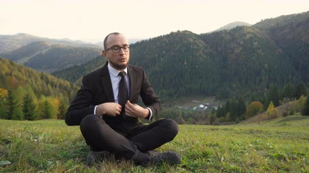 A Man In A Modern Office Suit Straightens His Tie In The Mountains. He Sits Cross-legged On A Hill. Business Concept Video