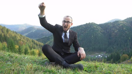A Man In A Suit And Glasses Came Up With An Idea. He Sits Cross-legged In The Mountains And Cannot Hide His Joy. Business Concept Video