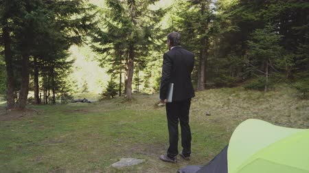 An Office Worker Went Out To Work After Camping In The Forest. He Holds The Laptop In His Hand And Leaves To Start A Busy Day. Business And Tourism Concept Video