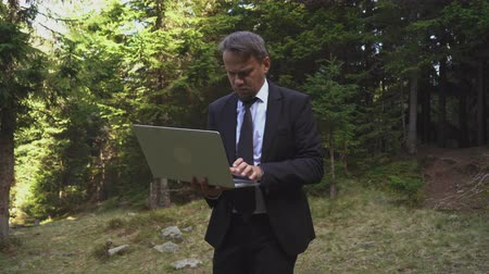 Successful Office Manager Is Working Outdoors On A Laptop. Hiker Businessman Is Typing Something On A Computer And Finishing His Working Day. Business And Tourism Concept Video