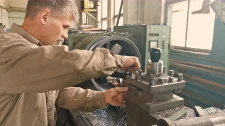 csavarkulcs : The Elderly Grey-haired Turner Works At The Turning Workstation In The Fabrication Shop.