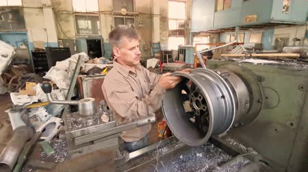 alaşım : The Turner Removes The Alloy Wheel Rim From The Turning Workstation After The Machining Process