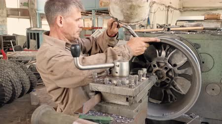 csavarkulcs : The Middle-aged Turner Installs And Centers The Alloy Wheel Rim With A Special Driving Tool