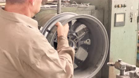 csavarkulcs : The Turner Removes The Alloy Wheel Rim From The Turning Workstation After The Machining Process