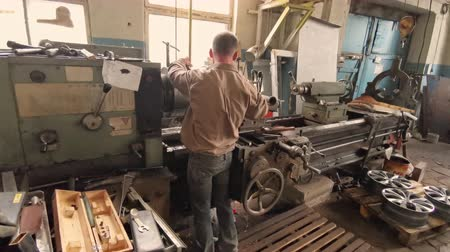alaşım : The Elderly Turner Standing With His Back Works At The Turning Workstation In The Production Department