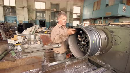 aro : The Turner Installs The Alloy Wheel Rim On The Turning Workstation In The Fabrication Shop Stock Footage