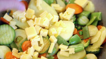 pieces of cheese : Placing pieces of cheese on vegetable mix  Stock Footage