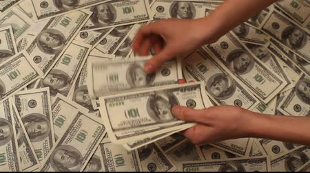 банк : Hand counting money to a us banknote on dollars money background Стоковые видеозаписи