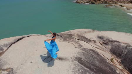 The girl is dancing near the sea. Panorama tribal fusion dance movement. Top down view whirling dancer in azure