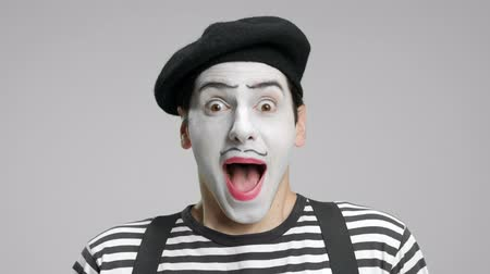 комедия : Close-up of a mime looking at the camera and smiling isolated on gray background