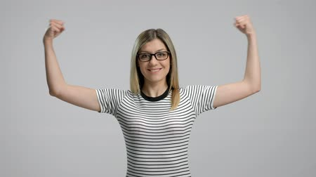 бицепс : Woman flexing her muscles isolated on gray background