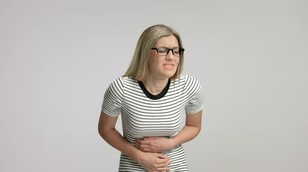 período : Young woman experiencing stomach pain isolated on gray background
