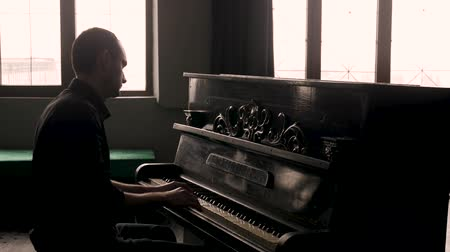 Side view. Pianist playing the vintage piano in old-fashioned interior.