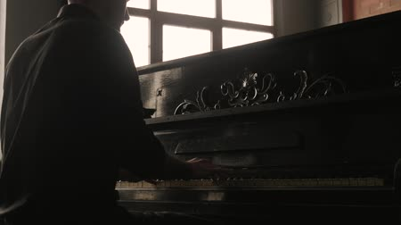 Vertical panorama. Pianist playing the vintage piano in old-fashioned interior.