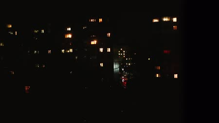 Night time lapse of Light in the windows of a multistory building. life in city