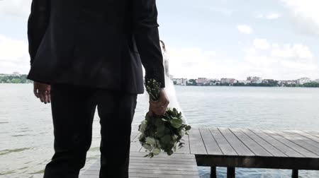 nowożeńcy : Rear view: The groom goes to the bride with a bouquet of flowers at the pier