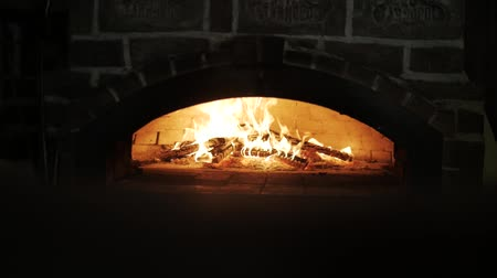 Vertical panorama: Fire in wood fired stone oven. Baking traditional pizza in a rustic cuisine. Fast food cooked in a wood-fired oven. DanItalian Pizza cooking in the oven with wood fire