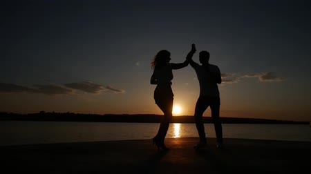 Young boy and girl dance salsa at sunset near the lake. Silhouette shooting. Slow motion