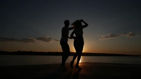 Young boy and girl dance salsa at sunset near the lake. Silhouette shooting.