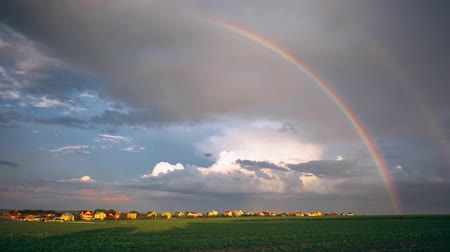 Rural landscape, rain clouds and rainbow, time-lapse.