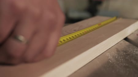 カーペンター : Male hands using a yellow tape measure to measure a piece of wood