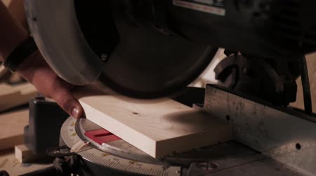 overall : Close up. The craftman is working on electric saw machine. Sawing a board.