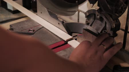 craftsperson : Close up. The craftman is working on electric saw machine. Sawing a board.