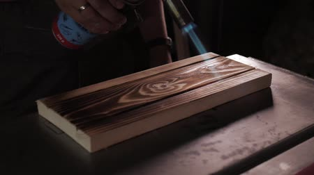lampa naftowa : Slow motion. Carpenter burns boards with a gas burner for blackening