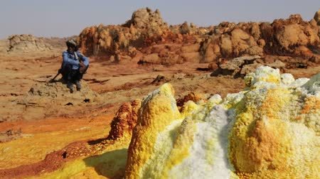 potash : ETHIOPIA, DALLOL-CIRCA DECEMBER 2017 - unidentified soldier looking for the tourist in volcano Stock Footage