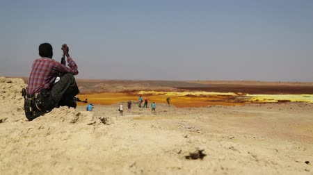phreatic : ETHIOPIA, DALLOL-CIRCA DECEMBER 2017 - unidentified soldier looking for the tourist in volcano Stock Footage