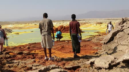 potash : ETHIOPIA, DALLOL-CIRCA DECEMBER 2017 - unidentified people walking in the volcanic depression Stock Footage
