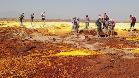 phreatic : ETHIOPIA, DALLOL-CIRCA DECEMBER 2017 - unidentified people walking in the volcanic depression Stock Footage