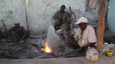 smithy : ETHIOPIA, HARAR-CIRCA DECEMBER 2017 - unidentified people working the metal in the forge