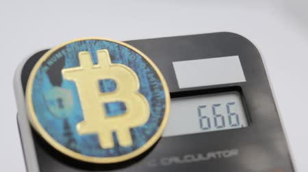 şeytan : near a calculator the coin of the bitcoin like concept of the future and investment 666 in the display Stok Video