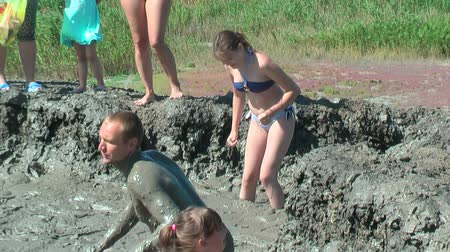boggy : Kuchugury, Russia - July 16, 2017: Azov scorching heat mud volcano. Woman and children take procedures with healing mud Stock Footage