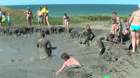 boggy : Kuchugury, Russia - July 16, 2017: Azov scorching heat mud volcano. People take procedures with healing mud Stock Footage
